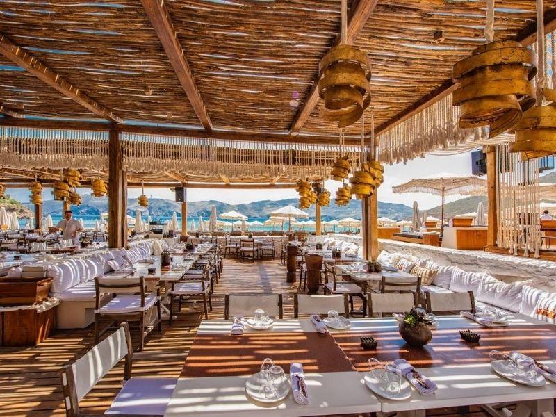 Principote beach club, Premium εμπειρίες στο Πριγκιπάτο της Μυκόνου. Στην προστατευμένη από τα μελτέμια παραλία του Πανόρμου, το βλέμμα του αρχιτέκτονα Αθανάσιου Κυρατσού, έχει εναρμονίσει το μαγευτικό τοπίο της αμμουδιάς με τα πολλαπλά επίπεδα του ατμοσφαιρικού χώρου.